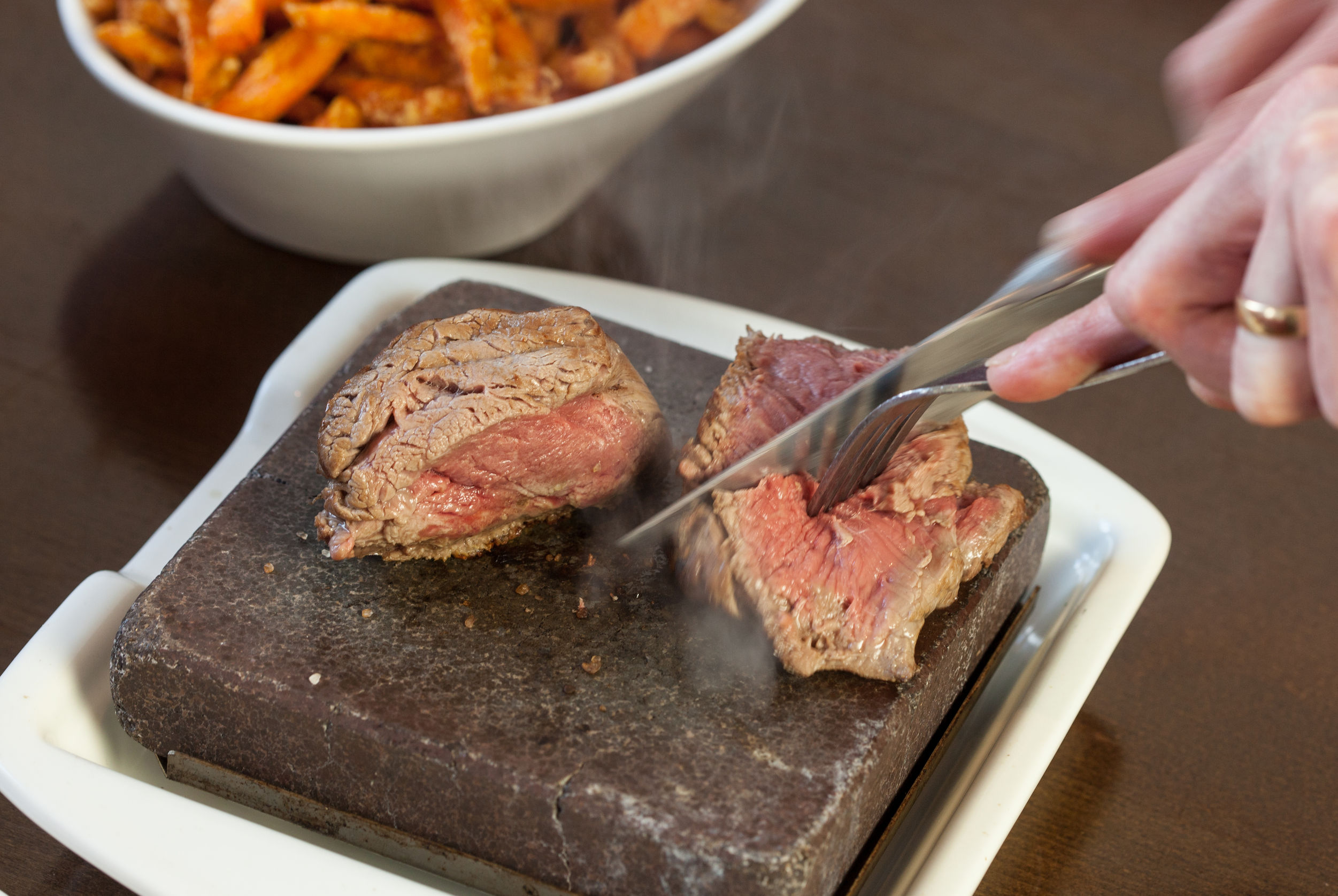 Steak sizzling on hot stone plate being sliced served in classy restaurant