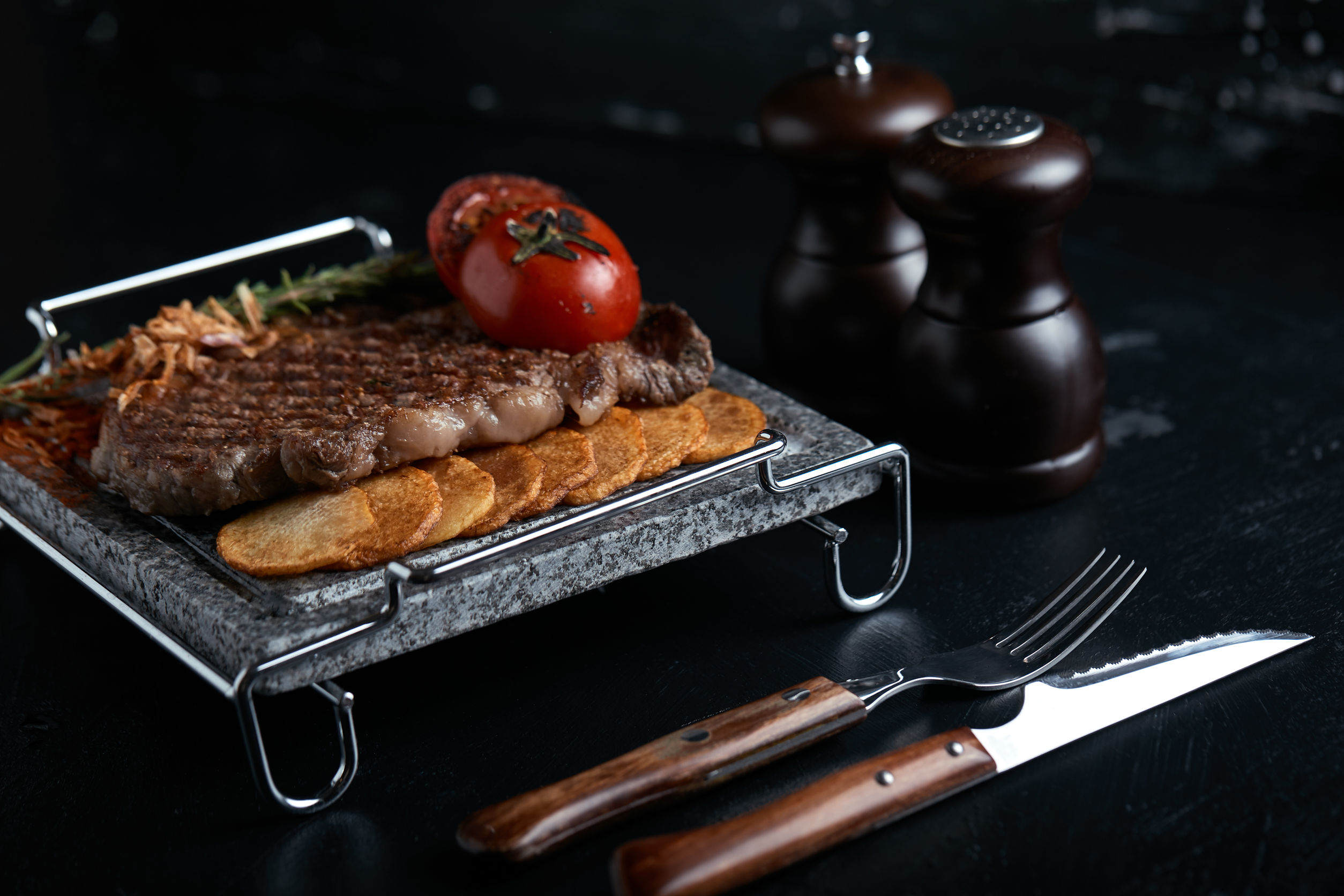 Grilled steak with knife and fork carved on black stone slate. Steak on a hot marble stone. Copy space, dark background, food fashion photo